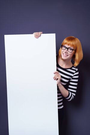 pert: Cute pert young redhead woman holding a blank white sign board with copy space peering around the side with a happy grin at the camera, over blue