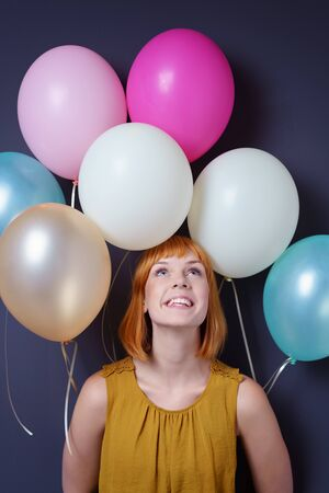 gleeful: Gleeful attractive young redhead woman surrounded by colorful party balloons looking up with a happy grin as she celebrates Stock Photo