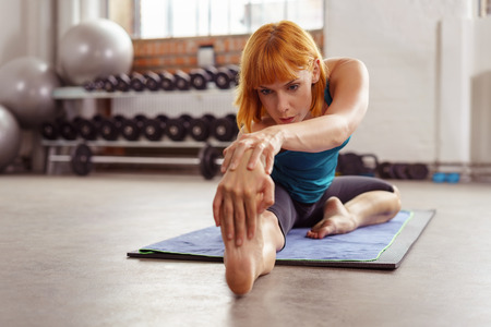 grasp: Supple fit young woman doing stretching exercises in a gym reaching forwards to grasp her bare foot with her hand , low angle frontal view with copy space