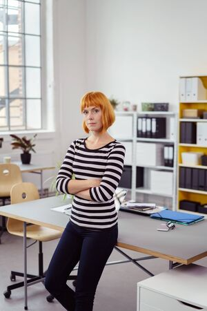 informal clothing: Confident serious young modern businesswoman in informal clothing standing with folded arms perched on the side of a table in the office