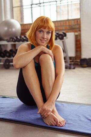 Pretty athletic barefoot young woman sitting on a yoga mat in a gym with her knees drawn up smiling at the camera