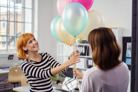 office party: Two female business partners or colleagues holding a bunch of multicolored party balloons with a happy smile in the office as they celebrate their success or anniversary Stock Photo