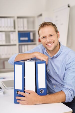clasping: Dedicated young businessman clasping three upright office binders as he sits at his desk smiling at the camera Stock Photo