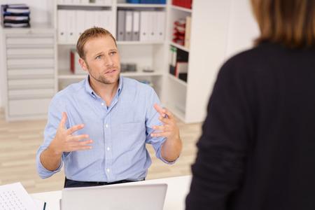 Imprenditore chiacchierando con un collega o supervisore in piedi sopra la sua scrivania gesticolando con le mani mentre si guarda con un'espressione seria