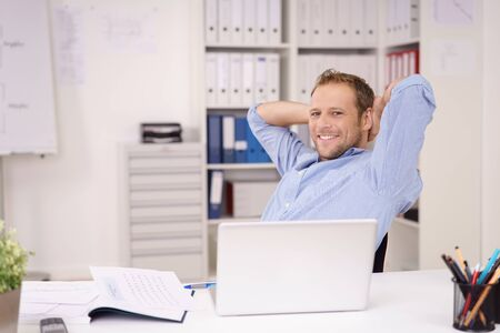 break from work: Smiling friendly businessman relaxing at the office sitting back in his chair at the office with his hands clasped behind his head Stock Photo