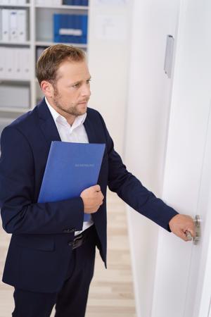 persona caminando: Apuesto joven solicitante de empleo masculina entrar o salir de una entrevista con su CV abrochado bajo el brazo y la mano en el pomo de la puerta Foto de archivo