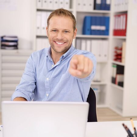 point of demand: Enthusiastic businessman pointing at the camera with a warm friendly smile as he sits at his desk in the office, focus to his face