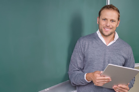 Happy friendly young teacher or pst graduate male student standing holding a tablet in front of a blank chalkboard