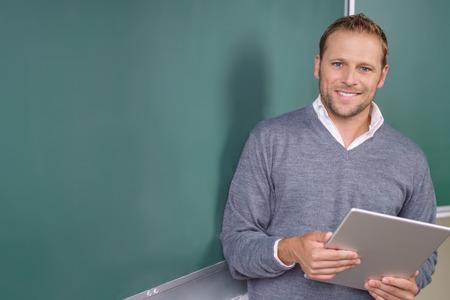 jeune professeur sympathique Heureux ou pst diplômé étudiant masculin, debout, tenue une tablette en face d'un tableau blanc Banque d'images