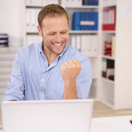 receives: Jubilant businessman cheering and making a fist as he receives good news of a business success