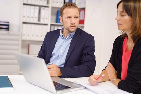 Uomo d'affari preoccupato l'ascolto di una collega di mezza età in cui siedono insieme a un tavolo in ufficio condivisione di un computer portatile