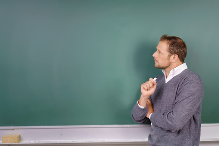 Thoughtful male teacher looking at a blank empty green blackboard with a stick of chalk in his hand and copy space for your text Фото со стока