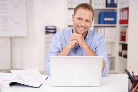 ノート パソコンのカメラに笑顔でオフィスで自分の机に座っているオープンのハイネック シャツで誠実な優しい青年実業家