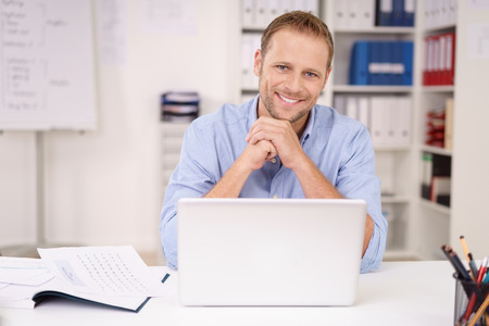Sincere friendly young businessman in an open necked shirt sitting at his desk in the office with a laptop smiling at the camera Stockfoto