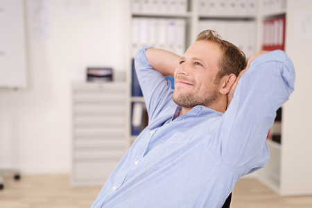Happy successful businessman relaxing back in his chair at the office with a beaming smile of satisfaction