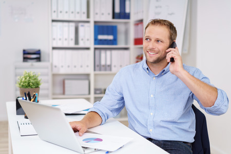 phonecall: Successful businessman talking on his mobile phone as he sits in the office smiling as he listens to the call Stock Photo