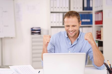 reacting: Happy businessman reacting to news on the laptop punching the air with his fists with a beaming smile to celebrate a success