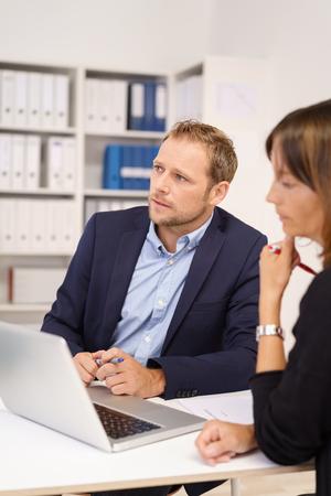 ejecutivo en oficina: Seus joven hombre de negocios sentado escuchando y viendo algo fuera de la pantalla mientras se sienta compartir un ordenador portátil con una compañera de trabajo Foto de archivo
