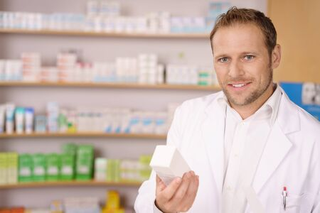 Handsome helpful pharmacist offering a box of medication to a customer with a friendly smile Stock Photo