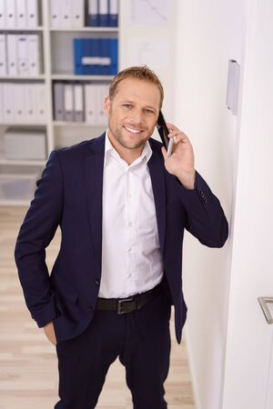 Young confident businessman with his hand in his suit pocket standing chatting on a mobile in the office with a pleased happy smile