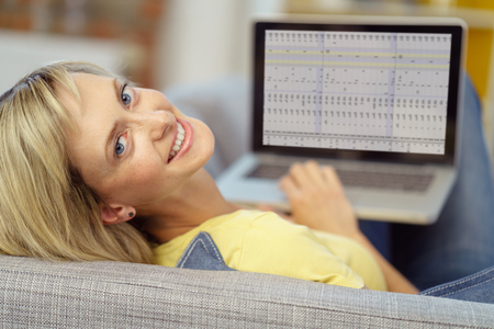 young woman smiling: Smiling young woman working from home lying on a sofa analysing a spreadsheet on a laptop computer turning to smile at the camera Stock Photo
