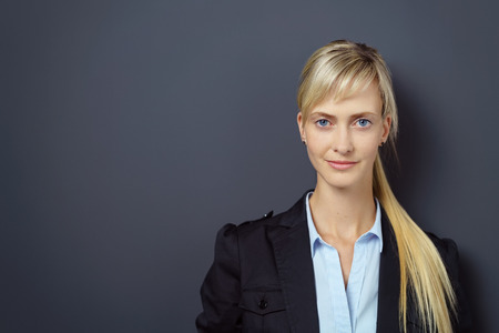 adult wall: Single slim young adult blond beautiful woman with grin and confident expression in front of dark wall with copy space