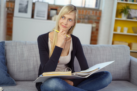 one room school house: Thinking young woman with thoughtful expression sitting cross legged on sofa with three ring notebook binder and pencil Stock Photo