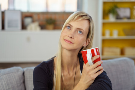 faraway: Woman sitting daydreaming as she relaxes on the couch at home over a mug of coffee staring into the air with a faraway expression