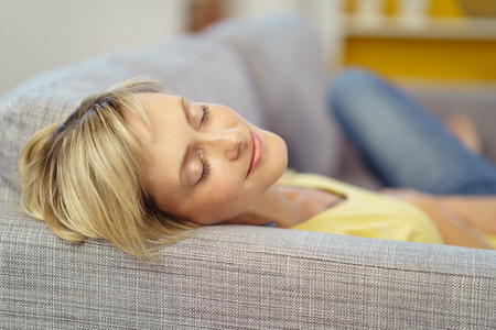 Relaxed young woman dozing off at home on the sofa with a serene expression and quiet smile