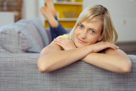 woman laying: Single young blond and blue eyed adult woman laying down on sofa with folded arms and copy space to the side