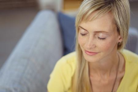 Aantrekkelijke jonge blonde vrouw die een stil ogenblik neemt aan het zelf zitten ontspannen op een bank thuis met gesloten ogen