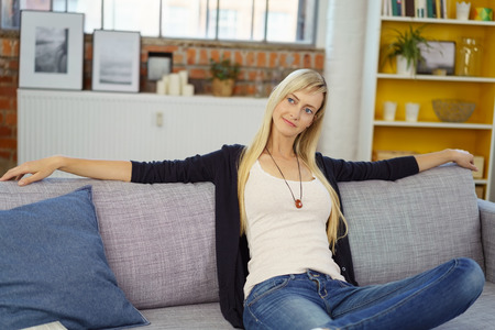 jeans apretados: Calm young blond woman in tight jeans leaning back with stretched out arms on sofa in small office with bookshelf in background