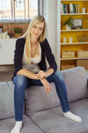 jeans apretados: Linda mujer rubia en pantalones vaqueros apretados sentado en el respaldo del sofá de pequeña oficina con el estante en el fondo Foto de archivo