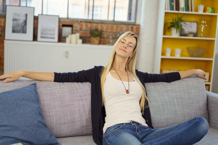 Relaxing young blond woman in tight jeans leaning back with stretched out arms on sofa while closing eyes in small office with bookshelf in background Фото со стока