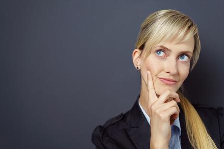 mujer sola: Mujer linda sobre fondo oscuro con el dedo en la barbilla mirando hacia los lados, como para ponderar o se preguntan sobre algo. Incluye copia espacio.