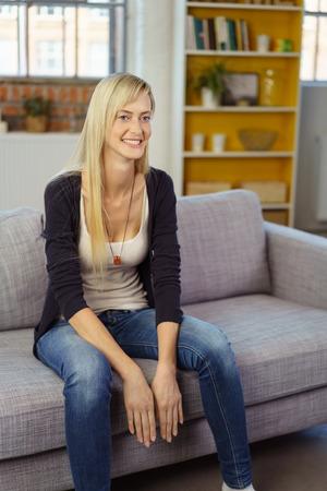 jeans apretados: mujer joven rubia en jeans ajustados que se sienta en el borde del sofá en la pequeña oficina con el estante en el fondo