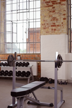 window bench: Fitness concept of barbell on bench press rack with copy space in area of window and brick wall