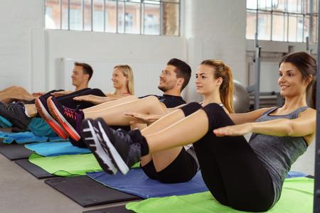 mujeres sentadas: Los hombres y las mujeres que ejercen al lado del otro sobre alfombras de yoga pose que llevan a cabo mientras se está sentado