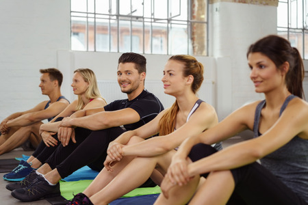 active adult community: Man in black athletic clothes looks toward camera while seated between others in sports gym