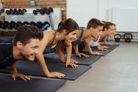 active adult community: Men and women on yoga mats do push ups and smile while exercising in sports gym