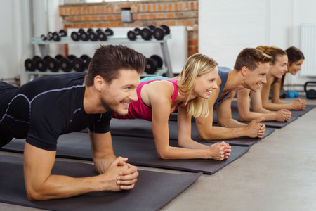 poised: Group poised in yoga pose on mats in neat row beside other exercise equipment