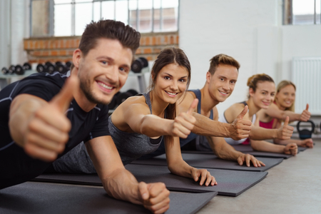 mat like: Group of men and women give the camera a thumbs up while on yoga mats in sports gym Stock Photo