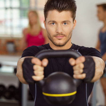 Single handsome man in beard and black compression shirt with serious expression holding kettle bell weight at indoor gym Stock Photo