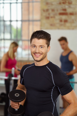 Handsome young man holding barbell in gym with other members obscured in background near window