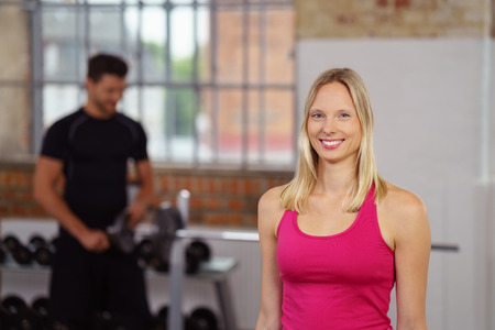 sleeveless top: Cute smiling woman dressed in pink sleeveless top standing near fitness trainer in front of barbell on rack in gym with copy space