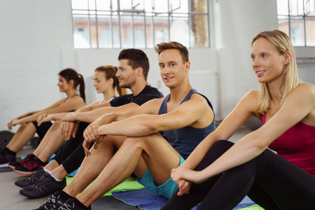 active adult community: Small group sits side by side on floor of gym while waiting to exercise Stock Photo