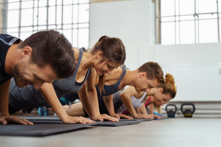 Group on floor of sports gym doing push ups near large windows and exercise equipment Stock Photo