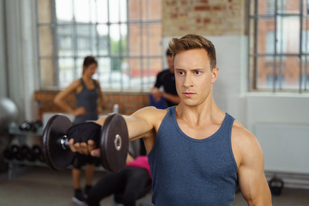 front raise: Single strong adult male in blue shirt performing front raise dumb bells exercises at gym