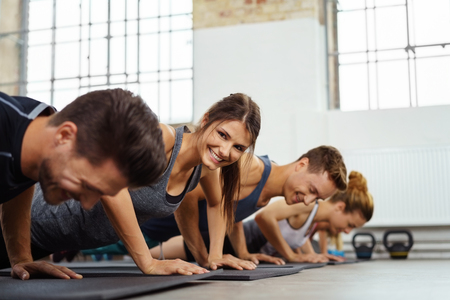 boot camp: Woman doing push ups smiles at camera while next to other athletes in exercise gym Stock Photo