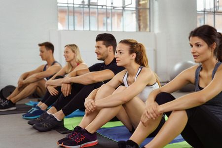 active adult community: Seated athletes hold knees while on gym floor having paused before more exercise Stock Photo